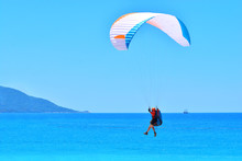Paragliding. Paraglider Landing On A Blue Sea Background.