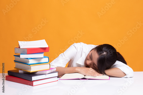 Foto  Exhausted Young Asian woman sleep with books on table.