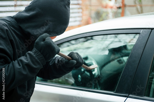 Vászonkép Close-up of a thief wearing balaclava breaking car window with crowbar