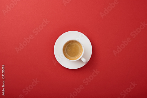 Cadres-photo bureau Cafe top view of white cup with coffee on saucer on red background