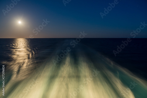 Photo Moon rising over wake and waves of cruise ship at sea with concept of leaving or