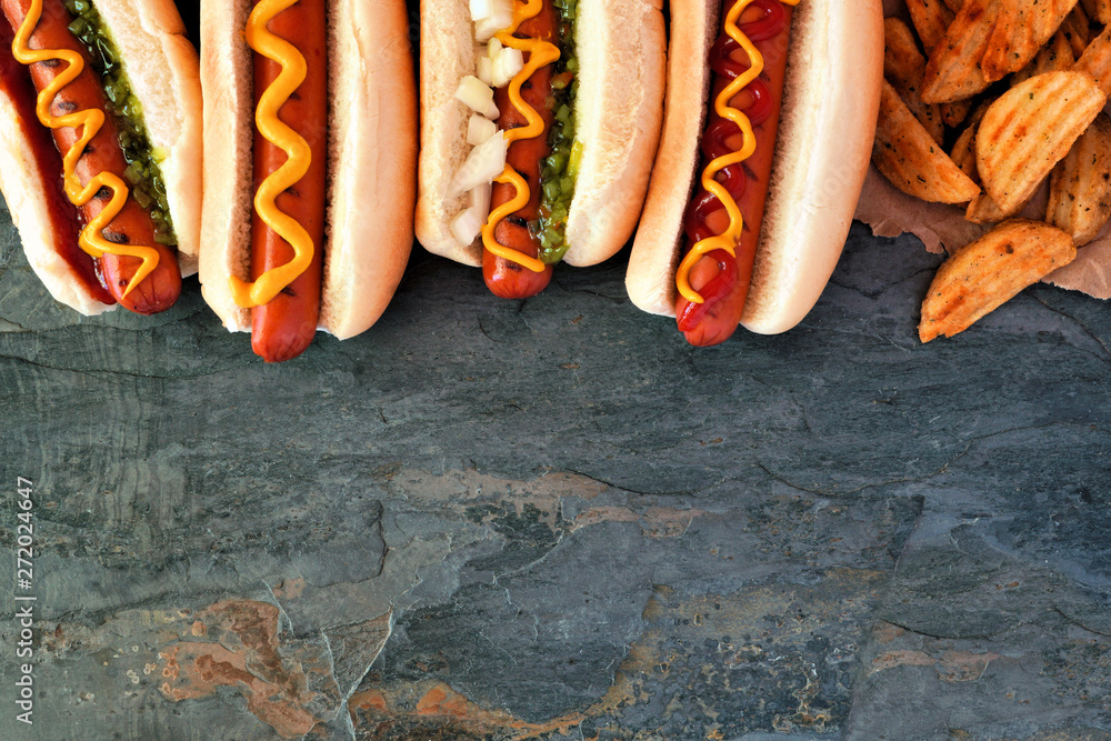 Fototapety, obrazy: Hot dogs with toppings and potato wedges. Top border, overhead view on a dark stone background with copy space.
