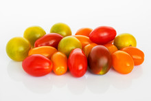 Mix Of Multicolored Cherry Tomatoes On A White Glossy Background. Heap Of Yellow, Orange And Red Small Tasty Tomatoes. Vegetarian And Healthy Eating.
