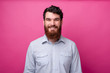 Portrait of smiling young bearded man in casual standing over pink background