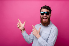 Portrait Of Amazed Young Man With Beard Pointing Away At Copyspace