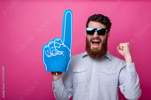 Fotomural Bearded guy with big blue fan glove, screaming and support his team