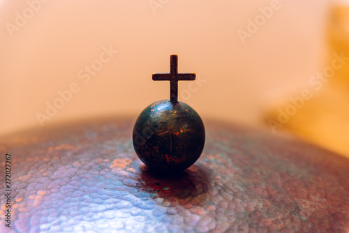 Photo Christian cross on a small metal ball, negative space.