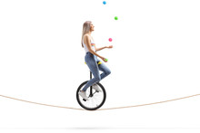 Young Woman Riding A Unicycle On A Rope And Juggling With Balls