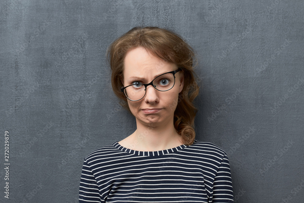 Fototapety, obrazy: Portrait of confused girl making silly face