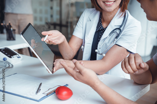 Fotografia  Professional doctor reporting medical results on mockup tablet white screen to male patient at clinic
