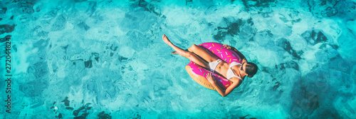 obraz dibond Beach vacation woman relaxing in pool float donut inflatable ring floating on turquoise ocean water background in Caribbean travel summer banner panorama. Girl in white bikini top drone view.