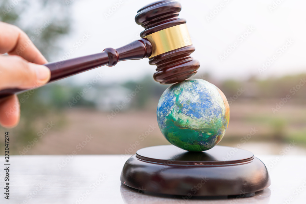 Fototapeta Earth destruction and destroy environmental by hand human concept. Judge gavel / world model should have legal force or certification for survival of all mankind with international Environment law