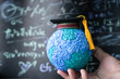 Education world, study learning achievement success in abroad global ideas. Graduation cap on models paper earth globe on hands, formula equation blackboard background. Congratulation in university