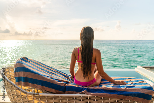 Fototapeta Sexy bikini woman from behind sitting back on lounger chair at luxury resort sun tanning at sunset by the hotel pool