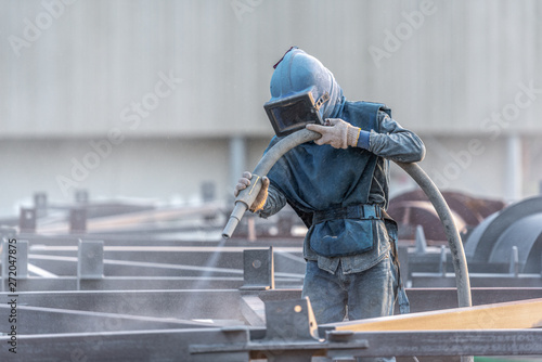 Valokuvatapetti Sand blasting process, Industial worker using sand blasting process preparation cleaning surface on steel before painting in factory workshop