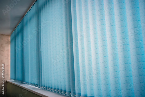 Stampa su Tela  Blue vertical blinds on the long window on balcony