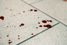 Conceptual Image With Blood On It Resting On Tiles On Floor