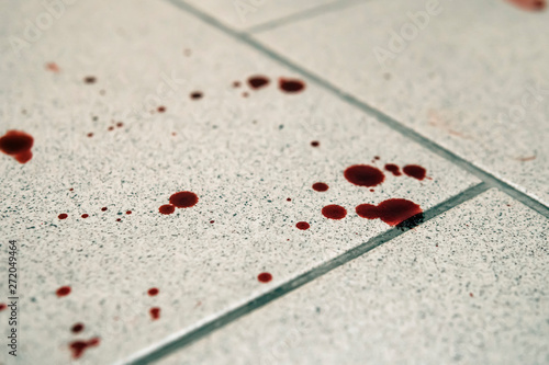 Fotografia  Conceptual image with blood on it resting on tiles on floor
