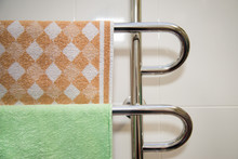 Modern Bathroom With Towel Warmer With Green And Brown Towel