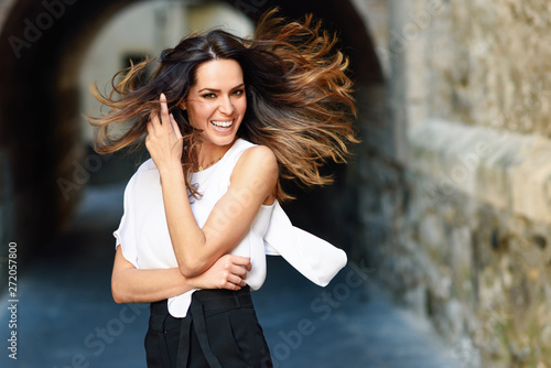 Photo  Young woman moving her long hair in urban background.