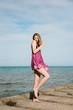 Sexy young woman in a short dress posing on the concrete pier of the sea