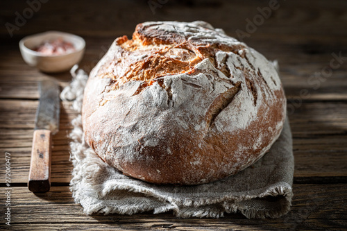 Fotografija Fresh loaf of bread with salt on wooden table