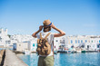 Leinwanddruck Bild - Traveler girl enjoying vacations in Greece. Young woman wearing hat looking at greek village with sea. Summer holidays, vacations, travel, tourism concept.