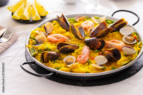 Seafood Paella with  prawns, clams and mussels on saffron rice with vegetables served in  traditional frying pan Fototapet