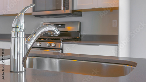 Panorama Modern kitchen interior with faucet and sink on the glossy countertop Canvas Print