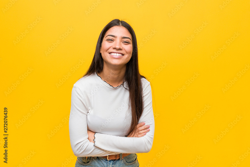 Fototapeta Young pretty arab woman against a yellow background laughing and having fun.