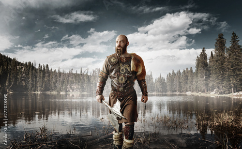 Photo  Handsome viking with axes standing at the lake