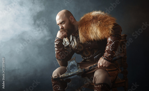 Thoughtful viking with axe sitting on chair Canvas Print
