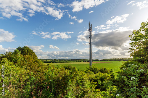 Leinwand Poster Sunset view British Mobile Operator Mast over field