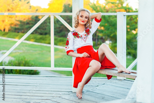 Fototapety, obrazy: Gorgeous young blonde woman with makeup, curly hairstyle in stylish red white dress posing on bench in garden arbor. sitting and looking away and smile. outdoor shot in the park at summer daytime