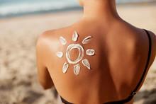 Woman Applying Sun Cream On Tanned  Shoulder In Form Of The Sun. Sun Protection.Sun Cream. Skin And Body Care. Girl Using Sunscreen To Skin. Female Holding Suntan Lotion And Moisturizing Sunblock.