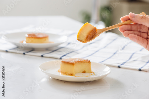 Woman's hand cutting homemade caramel custard pudding on white plate Wallpaper Mural