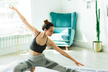 Young Attractive Smiling Woman Practicing Yoga In A Stylish Room