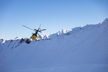 Helicopter Flying Over Snow-covered Mountain