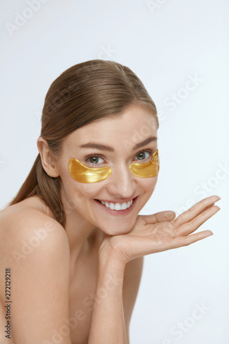 Skin care. Woman with under eye gold patch, beauty mask Fototapet