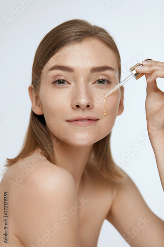 Skin care. Woman applying serum or facial oil on beauty face