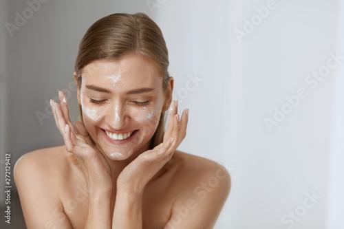 Photo sur Toile Les Textures Skin care. Woman applying facial cream on beauty face closeup