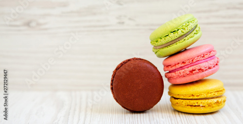 Fotobehang Macarons Sweet and colorful macarons on a white wooden background, side view. Copy space.