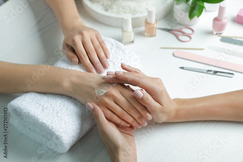 Montage in der Fensternische Entspannung Cosmetologist applying cream on woman's hand at table in spa salon, closeup