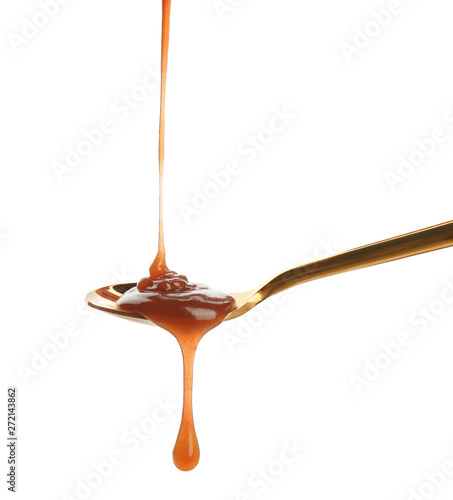 Fotografia  Tasty caramel sauce pouring into spoon isolated on white