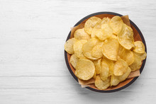 Delicious Crispy Potato Chips In Bowl On Table, Top View With Space For Text