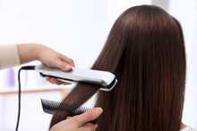Hairdresser Using Modern Flat Iron To Style Client's Hair In Salon