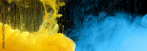 Acrylic blue and yellow colors in water. Ink blot. Abstract black background.