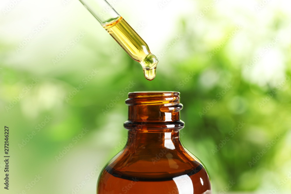 Fototapety, obrazy: Dripping natural tea tree essential oil into bottle on blurred background, closeup