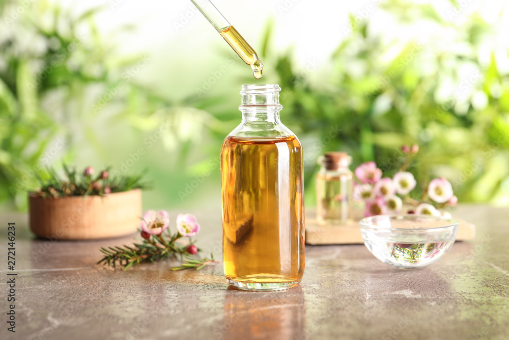 Fototapety, obrazy: Dripping natural tea tree essential oil into bottle on table