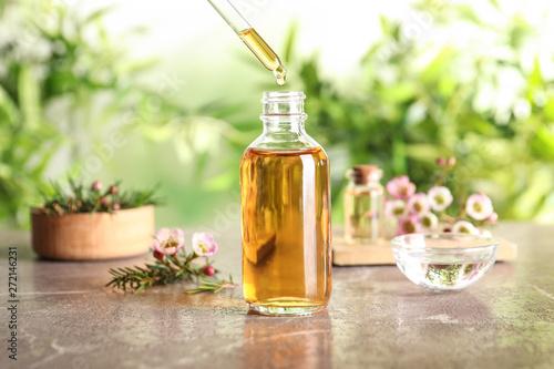 Fototapeta Dripping natural tea tree essential oil into bottle on table obraz